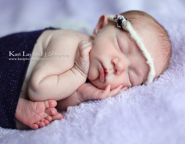 Newborn girl in purple, posing.