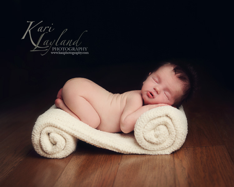 Newborn baby sleeping on rolled blanket.